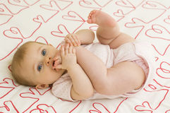 Baby on hearts Stock Images