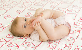 Baby on hearts Stock Photography
