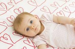 Baby on hearts royalty free stock photo