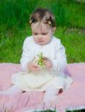 Baby in heldere kleren op een roze plaid op groen gras in het park stock fotografie