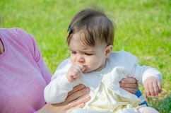 Baby in heldere kleren op een roze plaid op groen gras in het park royalty-vrije stock afbeeldingen