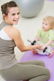 Baby helping mother lifting dumb-bell. At gym Stock Photography