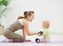 Baby helping mother lifting dumb-bells. Baby girl helping mother lifting dumb-bells Royalty Free Stock Images
