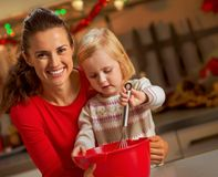 Baby helping mother make christmas cookies Stock Image