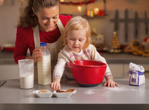 Baby helping mother make christmas cookies in kitchen Stock Photo
