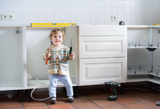 Baby helping to assemble kitchen in new home. Little baby helping to assemble a kitchen in a new home royalty free stock photo