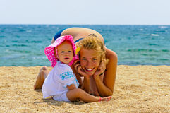 Baby with her mother on the beach Stock Images