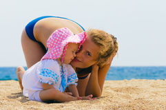 Baby with her mother on the beach Royalty Free Stock Photos