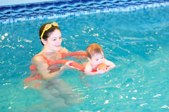 Baby with her mother in early swimming class. Baby playing with her mother in an early swimming class stock photos