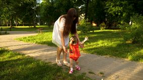 Baby with her mother makes first steps and falls to her knees, walking along road in park. Slow motion stock footage