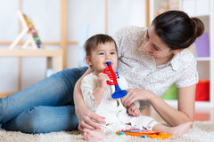 Baby and her mother play musical toys. Baby and mom playing with musical toys stock photography
