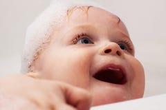 Baby in het bad met schuim bij het hoofd glimlachen Royalty-vrije Stock Afbeeldingen
