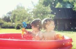 Baby het bespatten in de pool in openlucht Royalty-vrije Stock Afbeeldingen