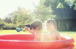 Baby het bespatten in de pool in openlucht Stock Foto's