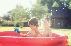 Baby het bespatten in de pool in openlucht Stock Fotografie