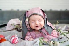 Baby het liggen op linnendeken en het dragen van een hoed in de vorm van een Paashaas met eieren en wilg vertakken zich stock foto's