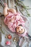 Baby het liggen op linnendeken en het dragen van een hoed in de vorm van een Paashaas met eierenwilg vertakken zich en Pasen-past royalty-vrije stock foto
