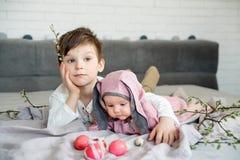 Baby het liggen op linnendeken en het dragen van een hoed in de vorm van een Paashaas met haar broer dichtbij eierenwilg vertakke stock afbeeldingen