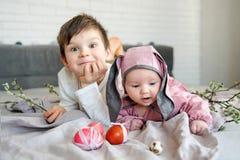 Baby het liggen op linnendeken en het dragen van een hoed in de vorm van een Paashaas met haar broer dichtbij eierenwilg vertakke stock foto's