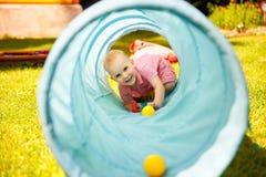 Baby het spelen binnen een stuk speelgoed tunnel Stock Foto's