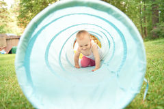 Baby het spelen binnen een stuk speelgoed tunnel Stock Afbeelding