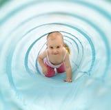Baby het spelen binnen een stuk speelgoed tunnel Royalty-vrije Stock Foto's