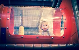 Baby het spelen binnen een stuk speelgoed tunnel Stock Afbeeldingen