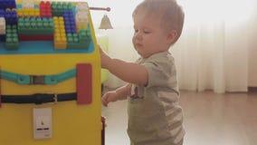 Baby het spelen met een stuk speelgoed klok Leuk weinig kind 2 stock videobeelden