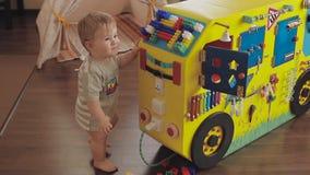 Baby het spelen met een stuk speelgoed klok Leuk weinig oud kind 2 jaar stock video