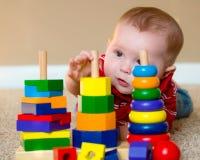 Baby het spelen met het stapelen van het leren stuk speelgoed Stock Afbeeldingen
