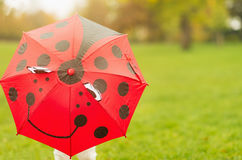 Baby hiding behind red umbrella Stock Images