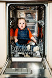 Baby hiding in dishwasher Royalty Free Stock Images