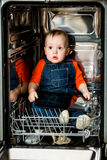 Baby hiding in dishwasher Royalty Free Stock Photography
