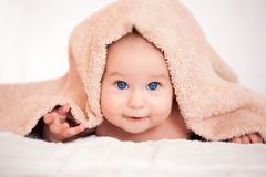 Baby is hiding under the beige terry towel Royalty Free Stock Image