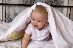 The baby is hiding under the cover and laughing royalty free stock photos