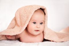 Baby is hiding under the white blanket. Baby girl is hiding under the white blanket Royalty Free Stock Photos