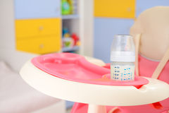 Baby high chair. Baby pink high chair and bottle with milk in baby room Royalty Free Stock Photography