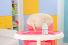 Baby high chair. Baby pink high chair and bottle with milk in baby room Stock Image