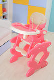 Baby high chair. Baby pink high chair on the floor of babys room Stock Images