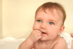 Baby high key. Baby lying on tummy on white bed sheets chewing his/her fingers stock image