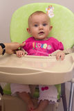 Baby in highchair Stock Images