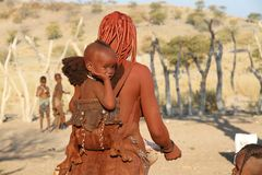 Baby himba grüßt die Kamera vom Rucksack, in dem seine Mutter ihn nimmt Lizenzfreies Stockfoto