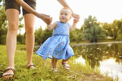 The baby with his mom takes the first steps in the park. stock images