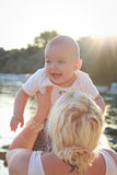 Baby with his mother enjoying a sunny evening. Sun flare in burned sky. Stock Photography