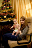 Baby and his mother near the Christmas tree Stock Image