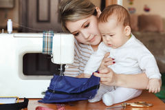 Baby with his mother seamstress, home, natural light, infant curiously looking to sewing machine. Child care and work at Stock Images