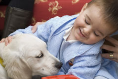 A baby with his white pet. Royalty Free Stock Photography