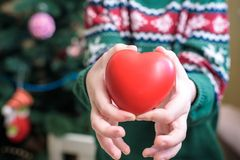 Baby hold red color heart in palm hands, love and health concept Royalty Free Stock Photo