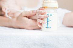 Baby holding a baby bottle with breast milk Royalty Free Stock Photography