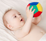 Baby holding a ball. Cute baby lying and holding a ball Royalty Free Stock Image